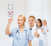 healthcare, medicine and technology concept - smiling young doctor or nurse pointing to red checkmark in checkbox