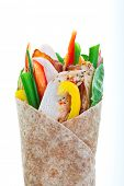 Healthy whole wheat turkey wrap on a white background.