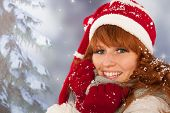 Portrait of woman in winter with snow and hat of Christmas Santa Claus