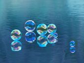 Soap bubbles, floating on water.