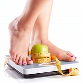 A Pair Of Female Feet Standing On A Bathroom Scale With Green Apple