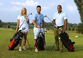 Happy young golfers standing on golf course, smiling, looking at camera.