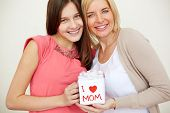 Teenage girl and her mom with giftbox looking at camera and smiling
