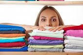 picture of cashiers  - young woman hiding behind a shelf with clothing - JPG