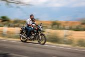 KERALA, INDIA - FEBRUARY 17: Man with child riding on a bike (blurred motion). Motorbike is the most