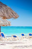 chairs and straw umbrellas on stunning tropical beach in dominican republic, punta cana