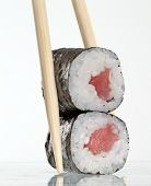 Holding tuna fish sushi roll with toothpicks on white background.