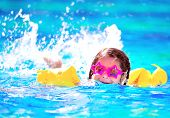 Cute little baby swimming in the pool, wearing funny sunglasses, enjoying summer weekend in aqua park, holidays and vacation concept