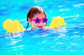 Cute little baby swimming in the pool, wearing funny sunglasses, enjoying summer weekend in aquapark