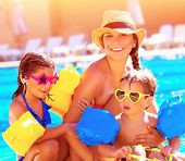 Happy family in summer vacation, young mother with two cute kids having fun near swimming pool on be