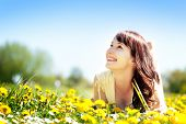 Young beautiful woman lying on grass full of spring flowers, looking happy at the sunny blue sky. Ha