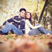 Love and affection between a young couple at the park in autumn season (selective focus with shallow