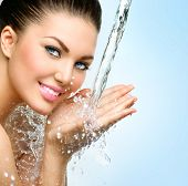 Beautiful Model Woman with splashes of water in her hands. Beautiful Smiling girl under splash of wa