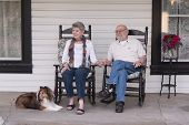 stock photo of sheltie  - An elderly married couple in their eighties watch the world go by from their porch with their sheltie dog by their side - JPG