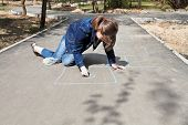 stock photo of hopscotch  - girl drawing hopscotch outdoors in sunny day - JPG