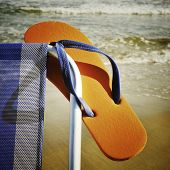 closeup of a deckchair with an orange flip-flop on the beach, with a retro effect