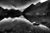 Reflective mountain lake landscape in black and white foreground stones