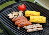 Grill bbq party with sausages, mushrooms and vegetables