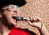 image of crazy hat  - Crazy rock and roller singer with a big black hat - JPG