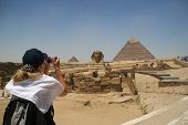 Blonde female turist takin picture of the Sphinx and the pyramids of Khafre (Chephren) and Menkaur (