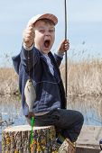 foto of caught  - Happy boy holding a fish caught in the pond - JPG