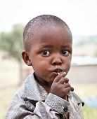 AFRICA, TANZANIA-FEBRUARY 9, 2014: Portrait on an African boy of Masai  tribe village looking to the