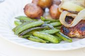 A barbecued meal of sugar snap peas, potatoes, onion and pork.