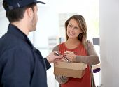 image of shipping receiving  - Woman sigining electronic receipt of delivered package - JPG