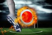 Football player kicking flaming japan flag ball against football pitch under stormy sky