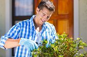 happy man pruning a shrub by house front door