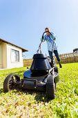 smiling male gardener pushing electric lawnmower at home garden