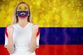 Excited colombia fan in face paint cheering against colombia flag in grunge effect