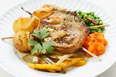 roasted pork medallion dish with carrot puree, pies and potatoes