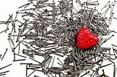 Red Love Heart On Pile Of Iron Nails
