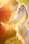 Young woman with favorite dog at sunset light.