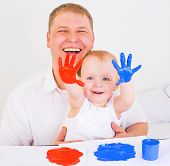 young father and his daughter playing with fingerpaints at home