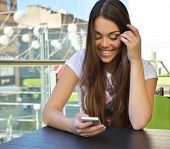 Beautiful cheerful teen girl eating ice-cream and using smartphone in outdoor cafe, urban teenager l