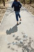 stock photo of hopscotch  - girl hopping in hopscotch on urban alley in sunny day - JPG