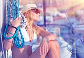 Young sexy sailor girl relaxing on sailboat, holding rope, enjoying sea cruise, active lifestyle, female in mild sunset light, summer vacation concept
