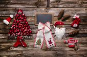 Festive natural christmas decoration: Red, white and wood with an empty sign for good wishes.