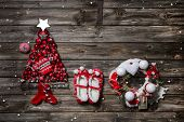 Wooden christmas background with red decoration and an empty sign or card for greetings.