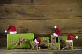 Christmas presents in apple green decorated with red santa hats on wooden rustic background. Idea for a gift certificate.