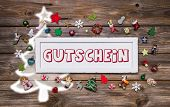 Wooden colorful christmas sign with text and decoration: gift certificate in german language.