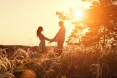 pic of hand kiss  - Young couple holding hands at sunrise - JPG