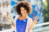 Afro woman giving a peace sign