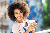 stock photo of afro  - Afro woman with coffee to go - JPG