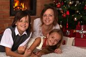 Happy Christmas family portrait - laying by the fire in front of xmas tree