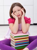 Young student with a headache - having lots to learn from many books