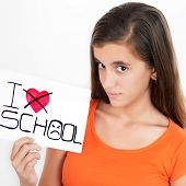 Teenage girl holding a sign with the words I hate school