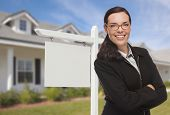 Attractive Serious Mixed Race Woman In Front of House and Blank Real Estate Sign.